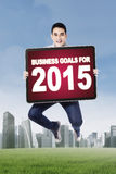 Young man jumping with business goals. Hispanic person jumping on the meadow while holding a board of business goals for 2015 Stock Photo