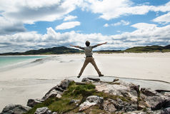 Young man jumping on a cliff with open arms. White sandy beach a Royalty Free Stock Image