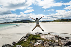Young man jumping on a cliff with open arms. White sandy beach a Stock Photos