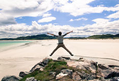 Young man jumping on a cliff with open arms. White sandy beach a Royalty Free Stock Photos