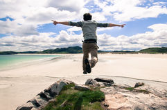 Young man jumping on a cliff with open arms. White sandy beach a Stock Photo