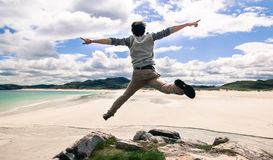 Young man jumping on a cliff with open arms. White sandy beach a Stock Photography