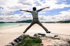 Young man jumping on a cliff with open arms. White sandy beach a Royalty Free Stock Photo