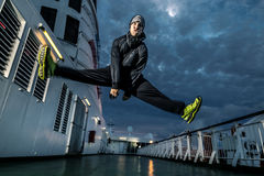 Young man jumping on the deck. Portrait of young and attractive man in green shoes on the deck. He is in a jump. Night scene. Cloudy sky. Funny face Royalty Free Stock Photo