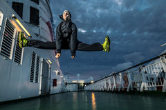 Young man jumping on the deck. Portrait of young and attractive man in green shoes on the deck. He is in a jump. Night scene. Cloudy sky. Funny face Stock Image