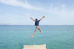 Young man jumping from the dock into the sea Royalty Free Stock Photo