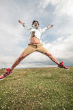 Young man jumping on a field full of flowers Royalty Free Stock Photo
