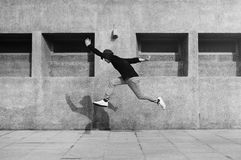Young man jumping in front of university campus building royalty free stock image