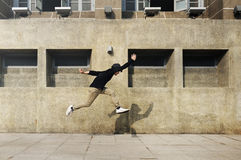 Young man jumping in front of university campus building Stock Photography