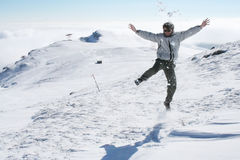 Young man jumping for fun in the snow Royalty Free Stock Photos