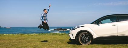 Young man jumping happy with car royalty free stock photo