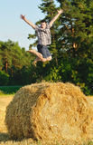 Young man jumping on a haystack Royalty Free Stock Image