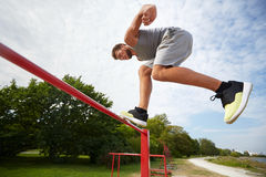 Young man jumping on horizontal bar outdoors Stock Photography