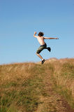 Young man jumping for joy. A young man with dark green shorts on running and jumping in the sky for joy Royalty Free Stock Photos