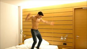 Young man jumping for joy on bed stock video