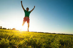 Young man jumping on meadow with dandelions Royalty Free Stock Images