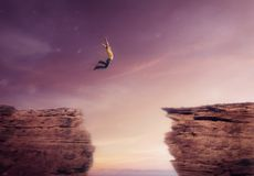 Young man jumping off a cliff Stock Photo