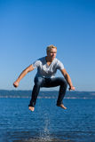 Young man jumping out of water Royalty Free Stock Images
