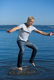 Young man jumping out of water Stock Images