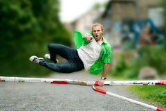 Young man is jumping over a barrier Stock Photo