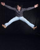 Young man jumping, over black background Stock Photo