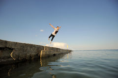 Young man jumping from a pier Stock Photos