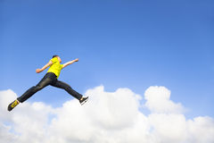 Young man jumping and pointing to sky Royalty Free Stock Photo