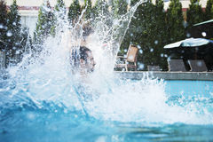 Young man jumping into a pool with water splashing all around him Stock Photo