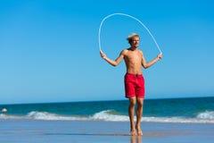 Young man jumping rope at the beach royalty free stock photos