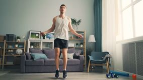 Young man jumping rope indoors at home wearing sportswear and sports shoes stock video