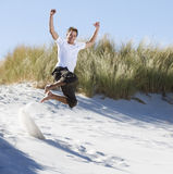 Young man jumping in sand dunes stock photos