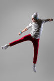 Young man jumping and screaming. Young modern style dancer in casual red pants working out, dancing and jumping with funny grimace, trying to kick something royalty free stock image