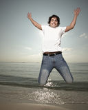 Young man jumping by the sea shore Royalty Free Stock Image