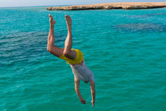 Young man is jumping into the sea Royalty Free Stock Images
