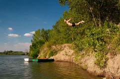 Young man jumping from the shore into the river Stock Photo