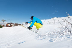 Young man jumping with snowboard Stock Images