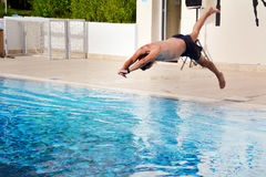 Young man Jumping in the  swimming pool. Young man  having  fun jumping in the pool-summer vacation Royalty Free Stock Photography