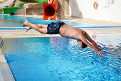 Young man Jumping in the  swimming pool. Young man  having  fun jumping in the pool-summer vacation Royalty Free Stock Images