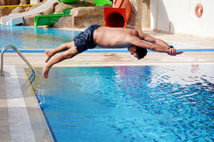 Young man Jumping in the  swimming pool. Young man  having  fun jumping in the pool-summer vacation Stock Image