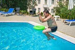 Young man jumping in swimming pool at resort.  Royalty Free Stock Photos