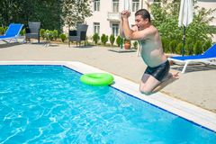 Young man jumping in swimming pool at resort.  Royalty Free Stock Images