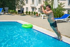 Young man jumping in swimming pool at resort.  Stock Image