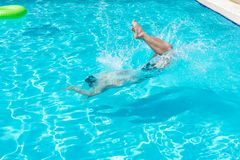 Young man jumping in swimming pool at resort.  Stock Photos