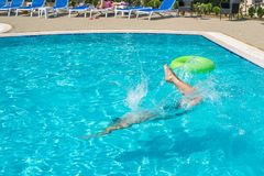 Young man jumping in swimming pool at resort.  Royalty Free Stock Photography