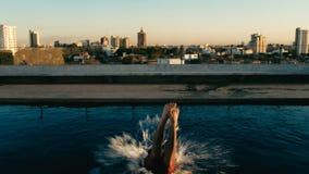 Young man jumping to the rooftop pool above the city. Santa Cruz, Bolivia - SEPT 5 2018: young man jumping to the rooftop pool above the city royalty free stock photos