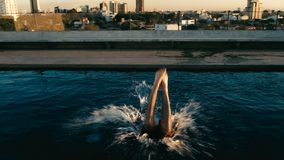 young man jumping to the rooftop pool above the city stock photography