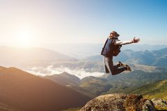 Young man jumping on top of a mountain against the sky.  stock images