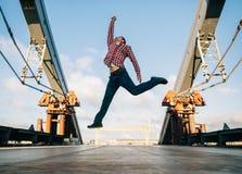 Young man jumping at the urban bridge stock images