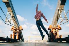 Young man jumping at the urban bridge stock image