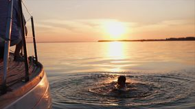 Young man jumping into the water from a sea yacht in the evening, sunset stock video footage